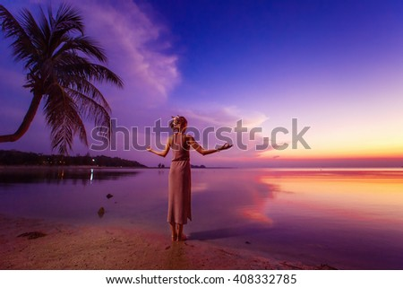 Young woman is standing relaxed at deep blue tropical sunset and meditating. - stock photo