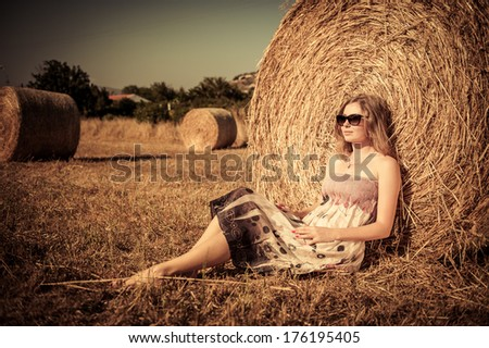 Young woman is taking rest on the cereal field - stock photo