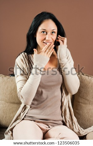 Young woman is talking on the phone and hearing surprise news,Surprised woman - stock photo