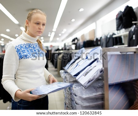 Young woman is thinking what shirt will be the best for her boyfriend. - stock photo