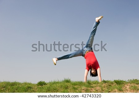 Young woman is turning a cartwheel - stock photo