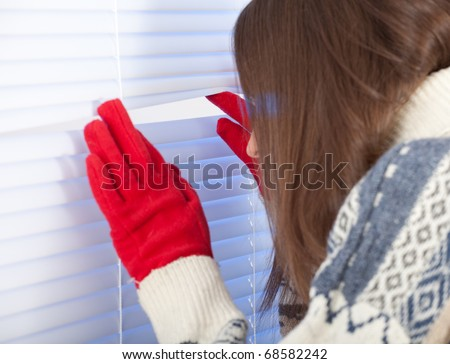 young woman is waiting with hope near window - stock photo