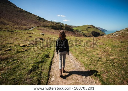 Young woman is walking along a path in the mountains - stock photo