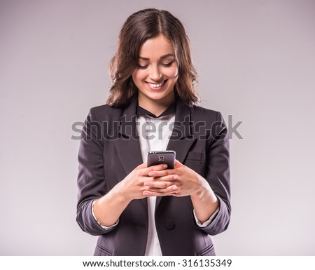 Young woman is writing a message with smartphone, standing on grey background. - stock photo