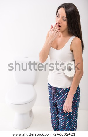 Young woman is yawning in toilet in morning. - stock photo