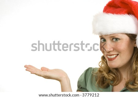 Young woman isolated on white holding hand out to side wearing a Christmas hat