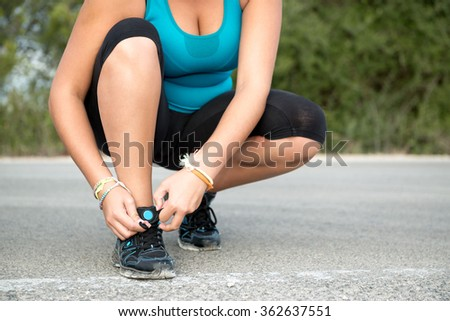 Young woman jogger tying hers shoes outdoors - stock photo