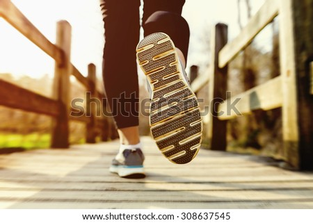 Young woman jogging across an old country bridge at sunset - stock photo