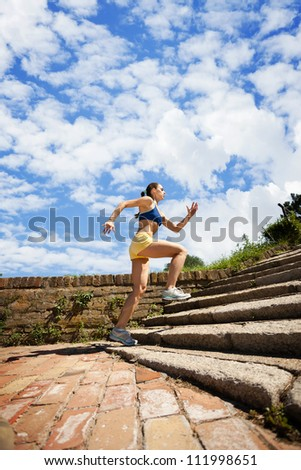 Young woman jogging in nature on steps - stock photo