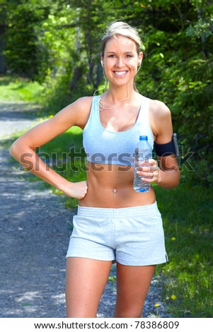Young woman jogging in park. Health and fitness. - stock photo