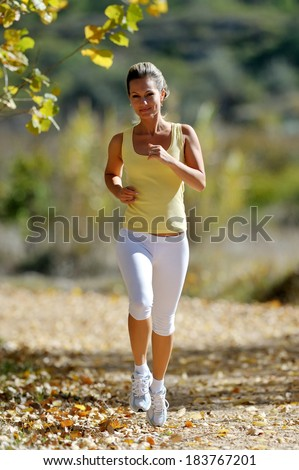 young woman jogging in the park in summer sunny day