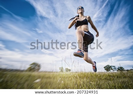 Young woman jogging in the summer park