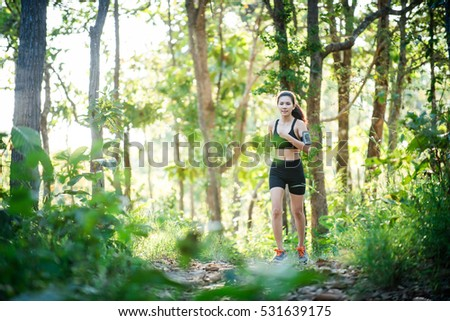 Young woman jogging on rural road in green forest nature.