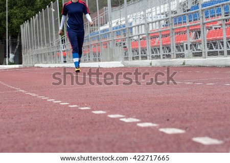Young woman jogging on stadium - stock photo