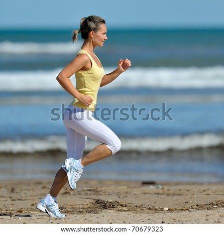 young woman jogging on the beach in summer - stock photo