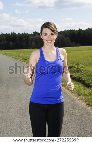 young woman jogging outdoors on the countryside - stock photo