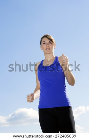 young woman jogging outdoors under a blue sky - stock photo
