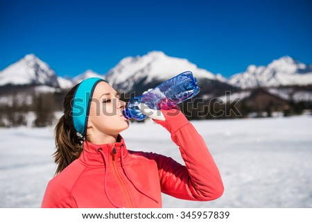Young woman jogging outside in sunny winter mountains - stock photo