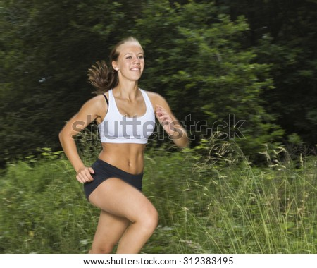 young woman jogging through a forest - stock photo
