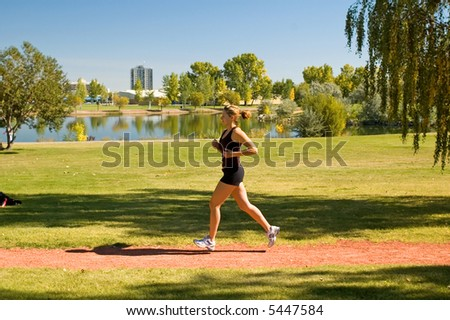 Young woman jogging through the park.