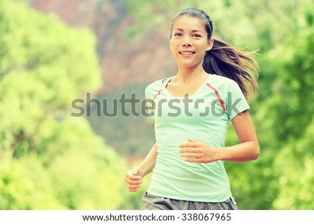 Young woman jogging while smiling. Beautiful mixed race Asian / Caucasian female is in sports clothing. Attractive lady is in park. - stock photo