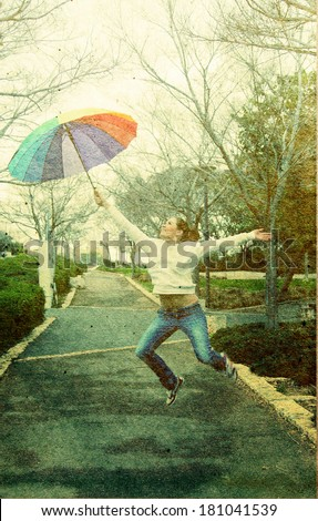 Young woman jumpimg with big rainbow umbrella. Photo in old image style - stock photo