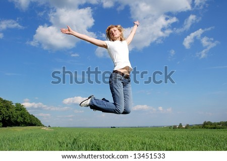 Young woman jumping at the background of blue sky and clouds in form of wings - stock photo