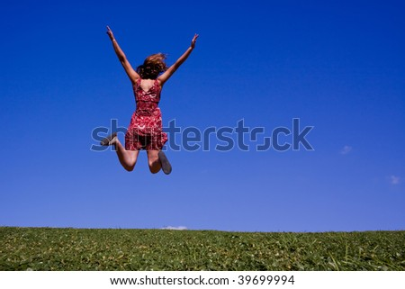 Young woman jumping for joy on a hillside in summer