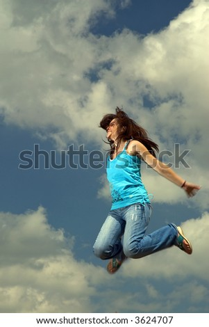 Young woman jumping high in the sky - stock photo