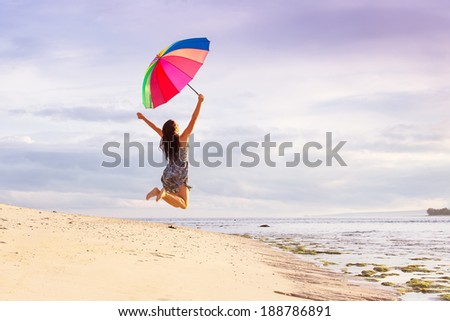 young woman jumping high with joy on the beach in summer with a colorful umbrella on a background of blue sky with clouds - stock photo