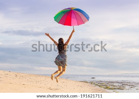 young woman jumping high with joy on the beach in summer with a colorful umbrella on a background of blue sky with clouds