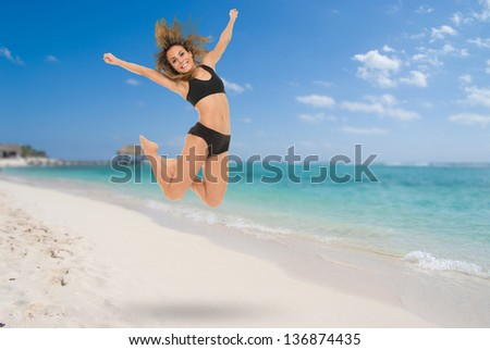 Young woman jumping in a Caribbean beach resort - stock photo
