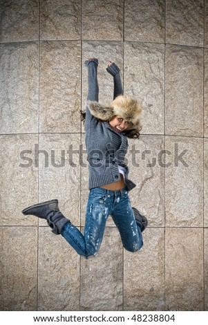 young woman jumping in fur hat against the wall