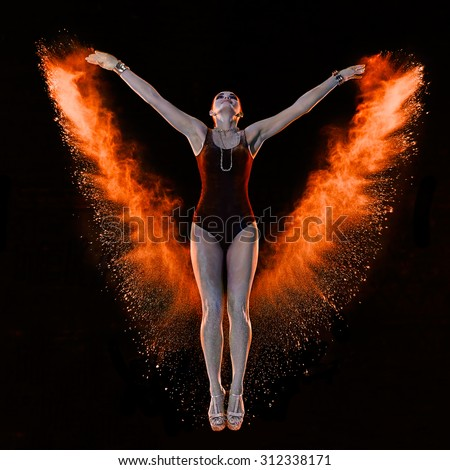 Young woman jumping in red flame powder cloud on dlack background - stock photo