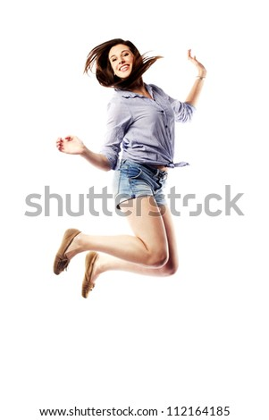 Young woman jumping in the air happily - stock photo