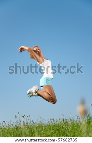young woman jumping in the air in front of a blue sky - stock photo