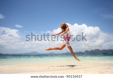 Young woman jumping on a beach - stock photo
