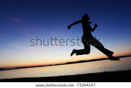 Young woman jumping on a beach at sunset