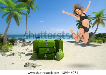 Young woman jumping on a tropical beach with a pile of luggage - stock photo