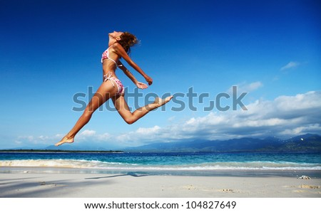 Young woman jumping on a white sandy beach and enjoying the tropical sun