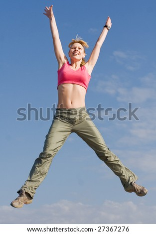 Young woman jumping on background of the sky