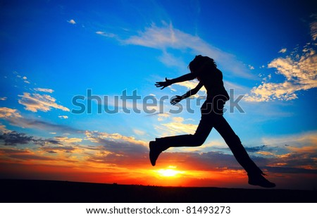 Young woman jumping on meadow on sunset background. - stock photo