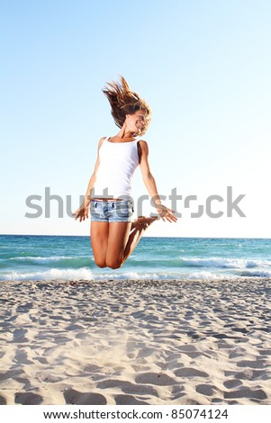 young woman jumping on sand beach - stock photo