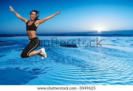 young woman jumping on the beach - stock photo