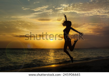Young woman jumping on the beach at sunset, silhouette shot