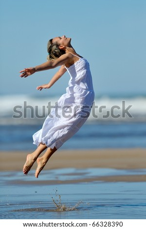 young woman jumping on the beach in summer - stock photo
