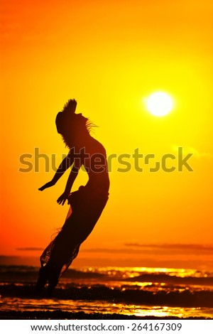 young woman jumping on the beach in summer evening - stock photo