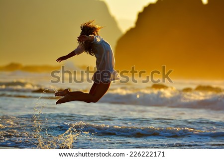 young woman jumping on the beach in summer sunset light - stock photo