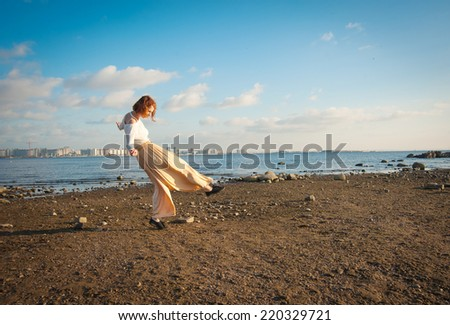 young woman jumping on the Gulf coast in the summer