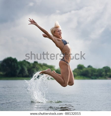 young woman jumping out of water - stock photo